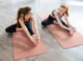 Kobiety rozciągające na matę do jogi