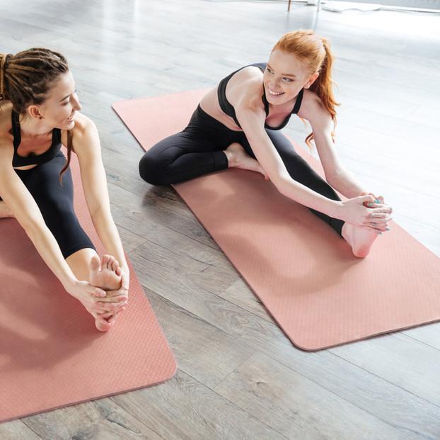 Kvinder Strækker på yogamåtte