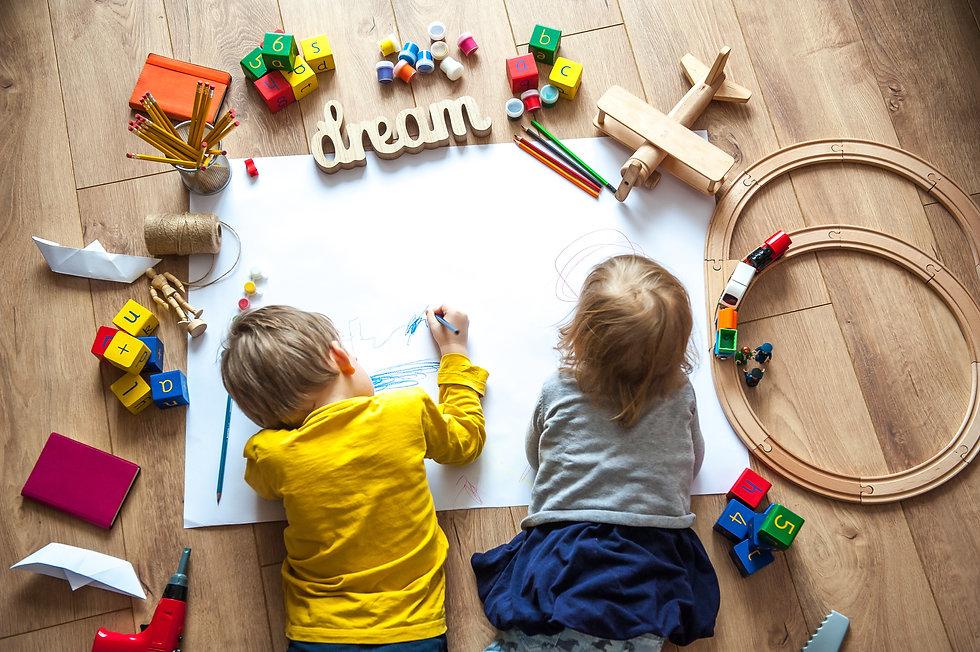 Preschool boy and girl play on floor wit