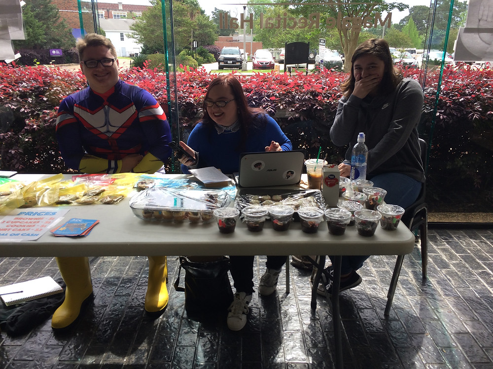 Three undergraduate students--one male and two female--sit behind a table of baked goods they're selling to raise money for a writing club on campus.