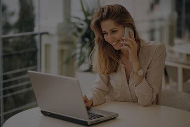 business-woman-working-laptop-talking-ph