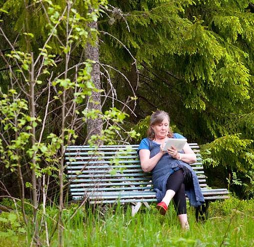 Klara Yvonne Klingspor sitter på en bänk i skogen med block och penna