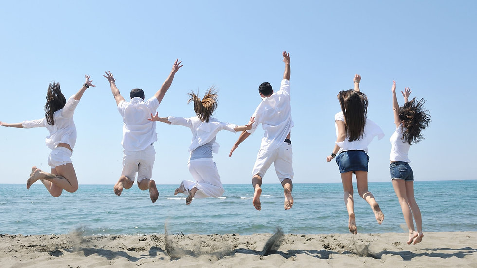 People jumping for joy on a beach overlooking the ocean.