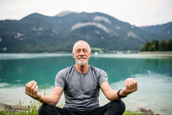 A mature man meditating with a view of water and mountain behind him.