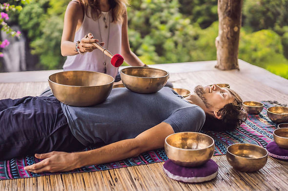 A women performing sound bowl therapy on a man.