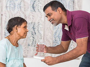 Healthcare professional providing patient with a glass of water
