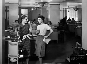 black and white picture of two office workers near a water cooler