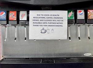 soda pop machine with a covid-19 coronavirus sign attached