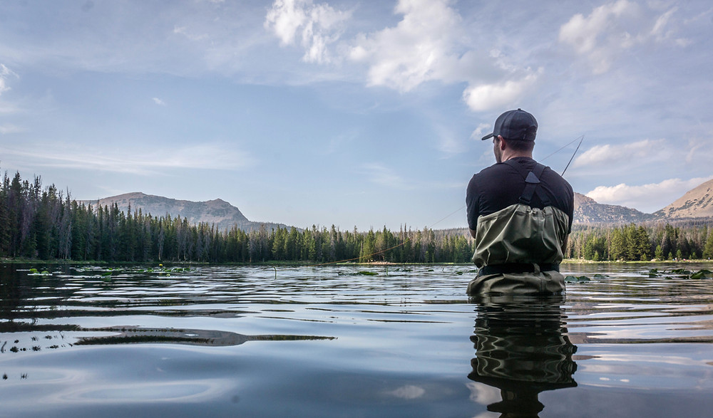 A man standing waste deep while fly fishing in Lake Dillon