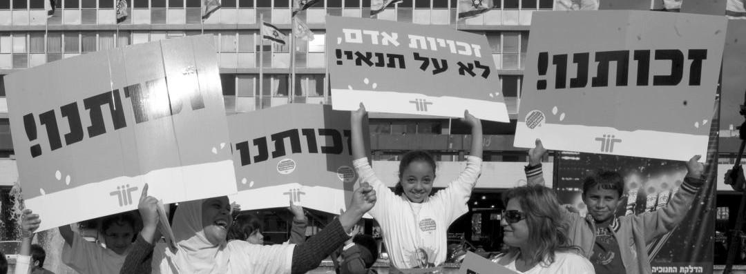 """מפגינים נושאים שלטים: """"זכותנו"""", """"זכויות אדם - לא על תנאי"""""""