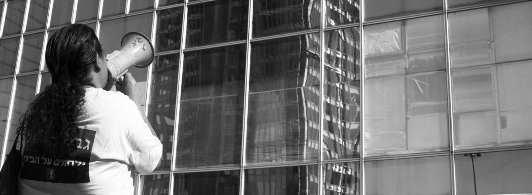 אילוסטרציה - מפגינה קוראת במגאפון מול בניין משרדים