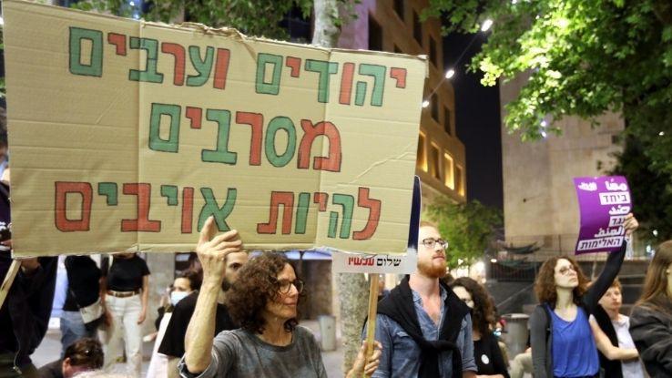 מפגינה עם שלט: יהודים וערבים מסרבים להיות אויבים