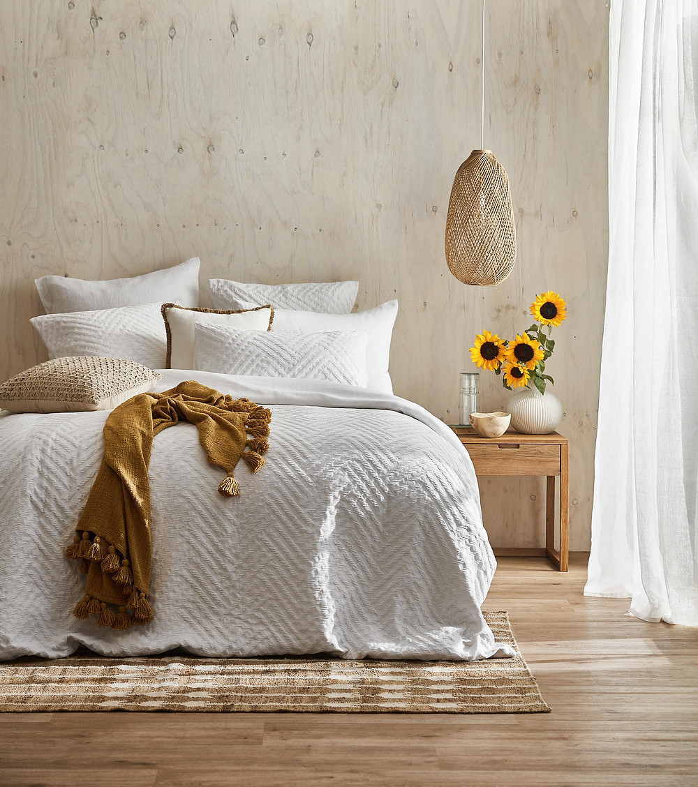 Light bright bedroom with white quilt cover and ply walls. Sunflowers, woven pendant and a jute rug.