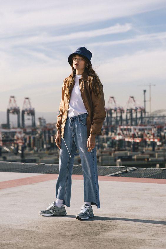 Normcore girl wearing denim bucket hat, jeans and khaki jacket