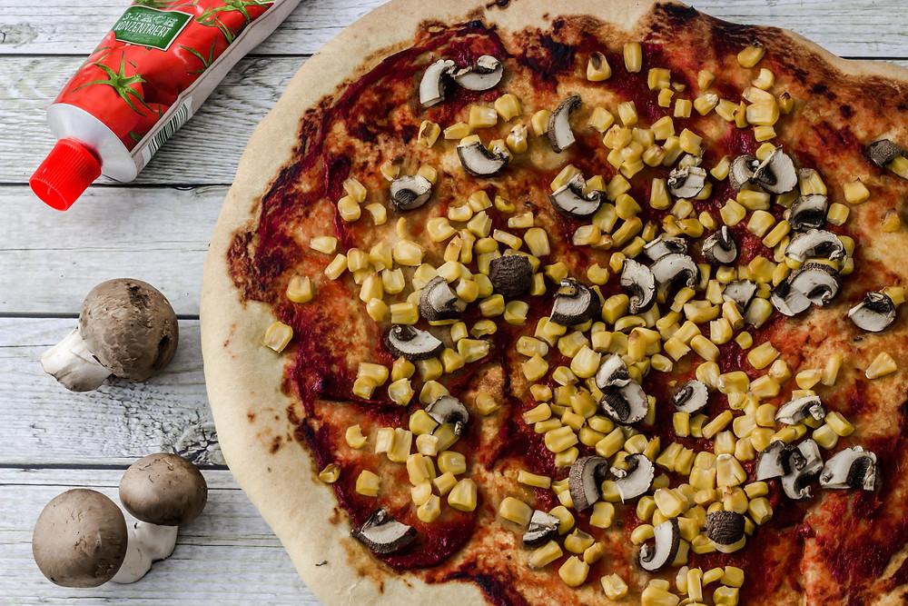 vegane Pizza mit Mais und Champignons