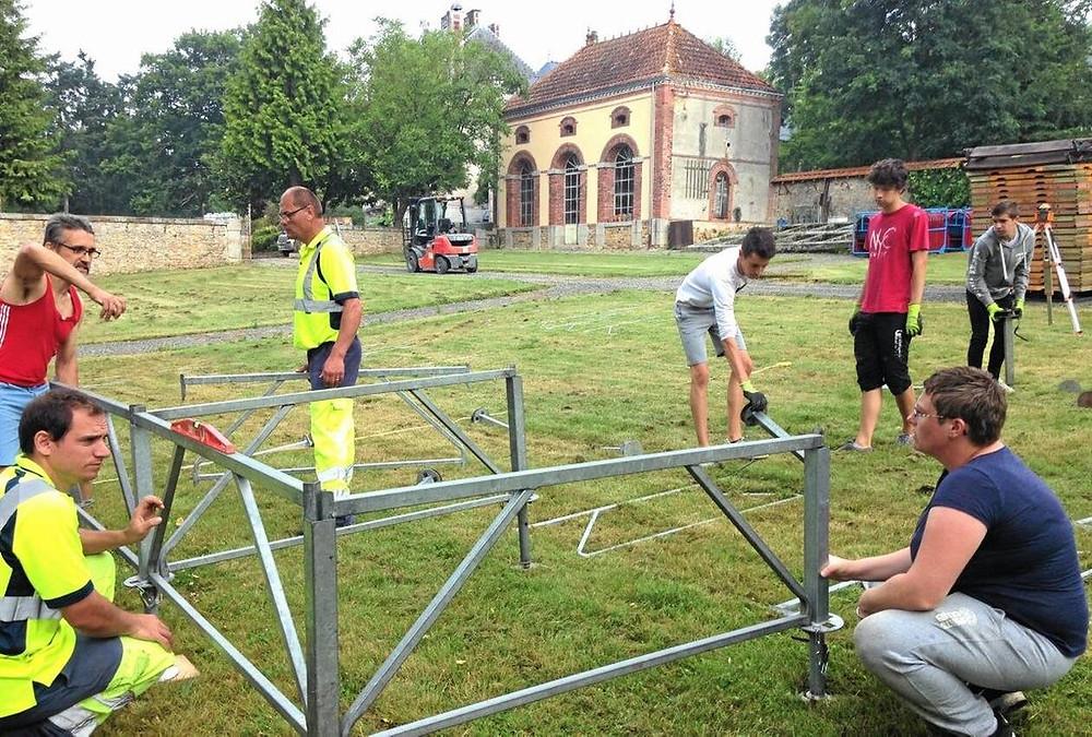 Installation des tréteaux dans le parc du Château de la Roche, avec l'aide des jeunes.