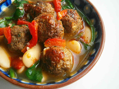 Merguez inspired meatballs with butter beans, spinach, peppers & harissa