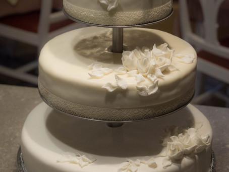 3 stöckige Hochzeitstorte weiß eingedeckt und Rosen