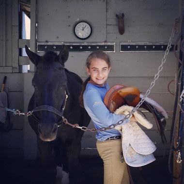 Holding saddle with black horse.jpg
