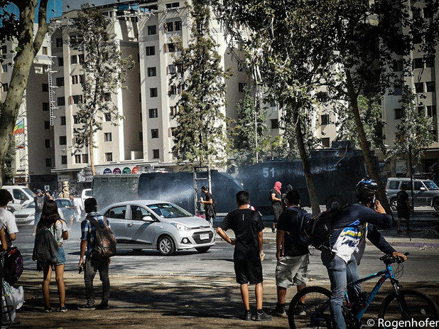 As police and protesters clash, ordinary urban life continues around them.