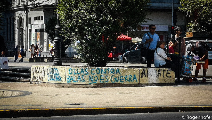 """Above the slogan """"pots against bullets is not war"""" life seems to continue as normal. The banging of pots is a common for of protest across Latin America."""