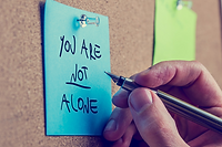 You are not alone written on a post-it note