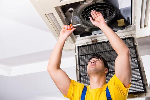 Repairman repairing ceiling air conditio