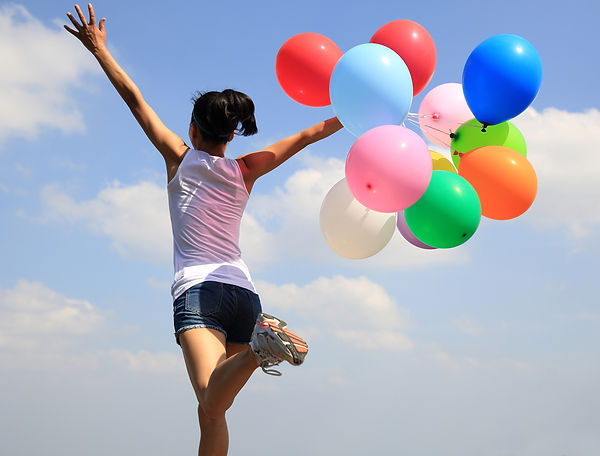Girl running with coloured Balloons