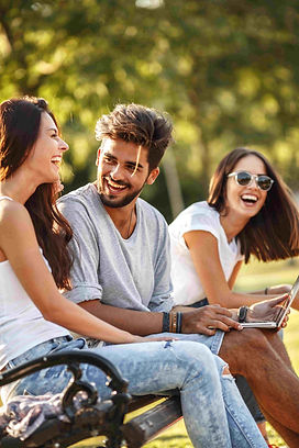 Friends on park bench with laptop