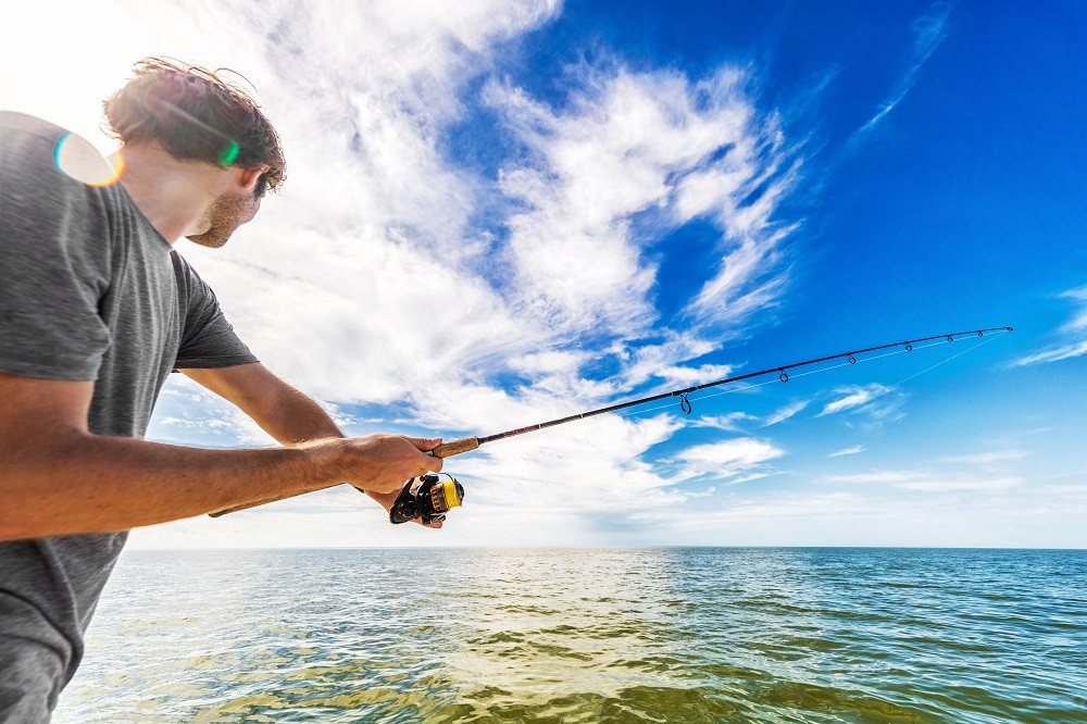 Young man casting fishing line
