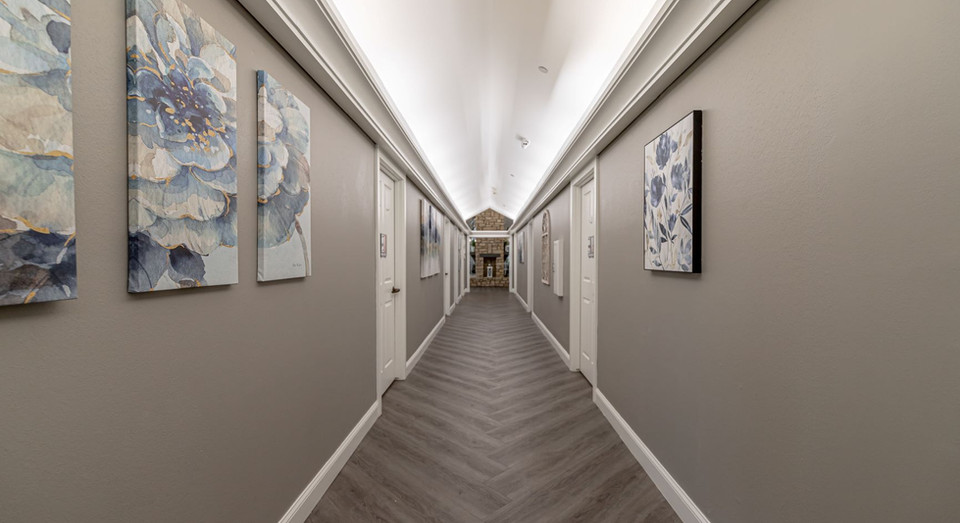 Long bright hallway with vaulted ceilings to resident rooms