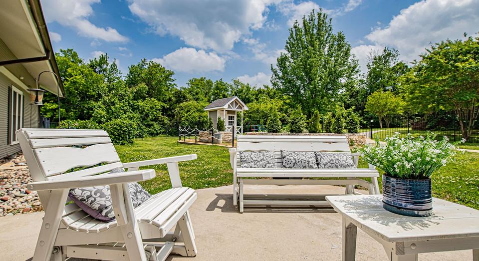 Comfortable patio furniture on a bright, sunny day, near outdoor garden