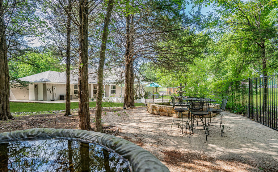 Patio in wooded space with bird bath, table and fountain