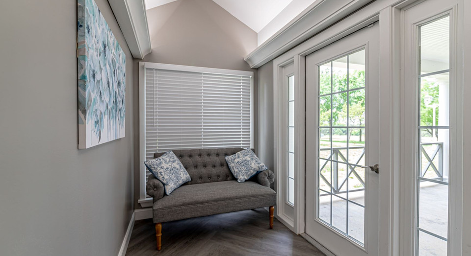 Love seat at end of hallway next to full length windows and door to outside patio