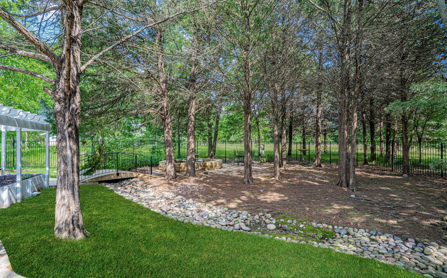 Wooded backyard with rock stream and private seating areas