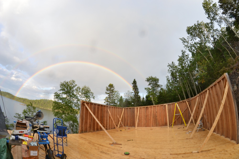 Double rainbow over the water on a diy cabin build installing walls