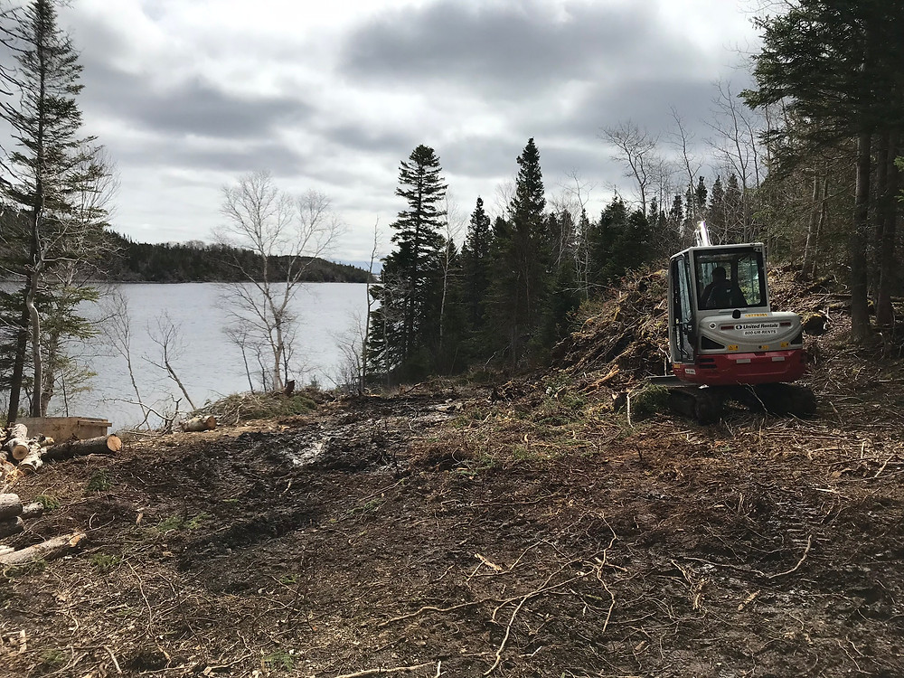 A mini excavator with a buster was used to break apart the rock on our DIY cabin build lot