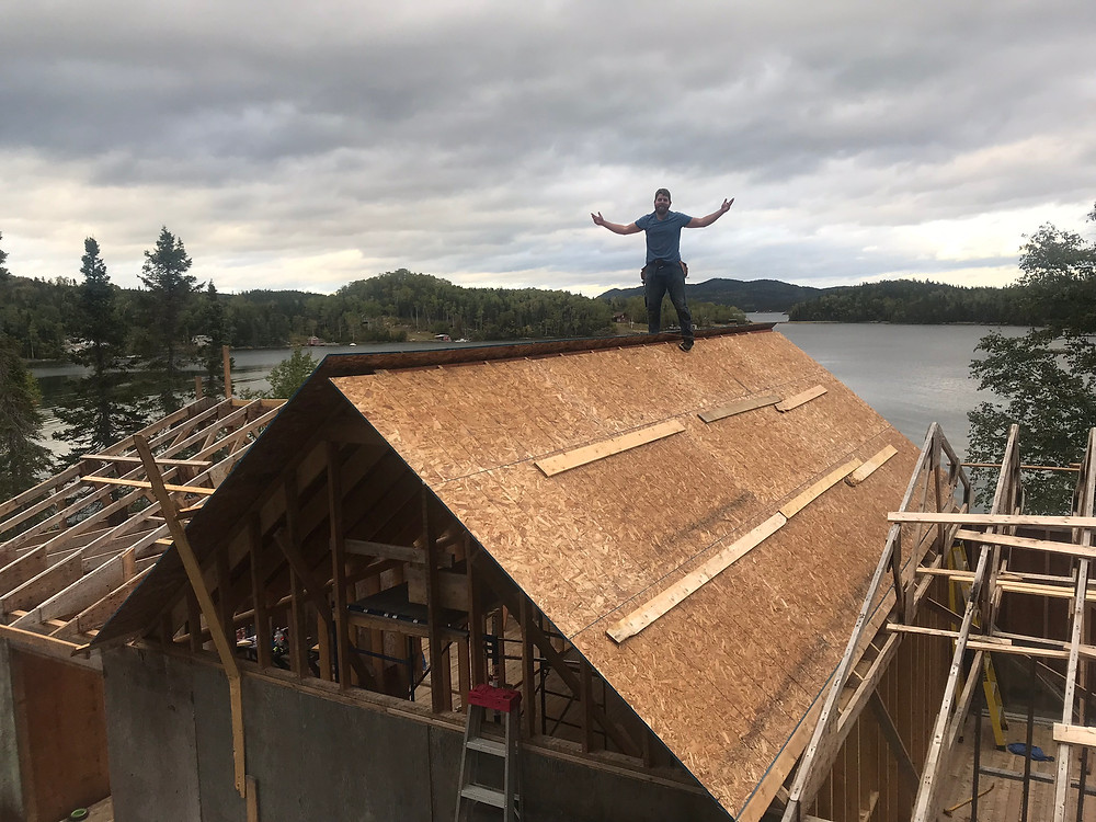 A Man on top of a diy cabin roof build