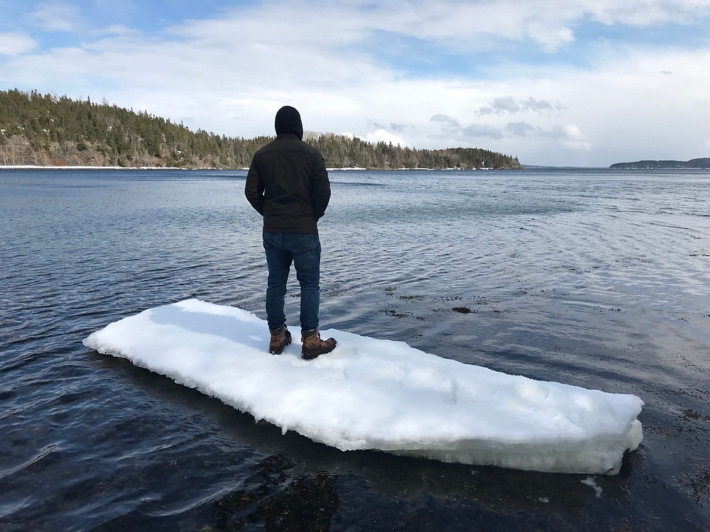 Mike standing on a piece of ice that grounded out on the beach by our land.