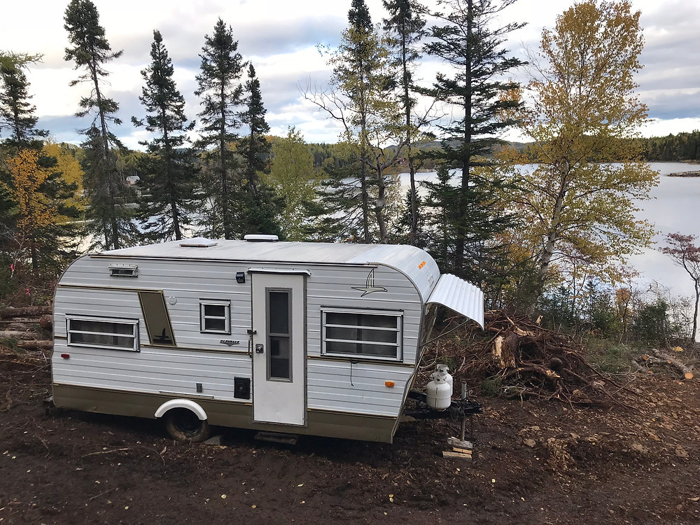 A 1960s Camper parked near the ocean at our diy cabin build