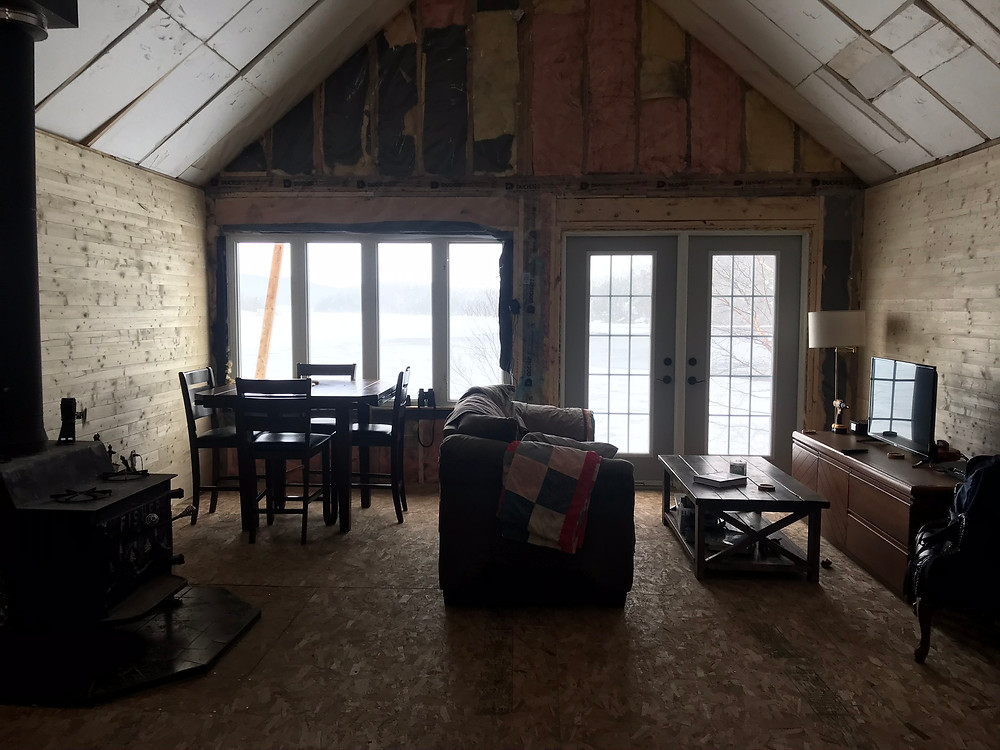 DIY cabin Living room with a view of the ocean through large window and door