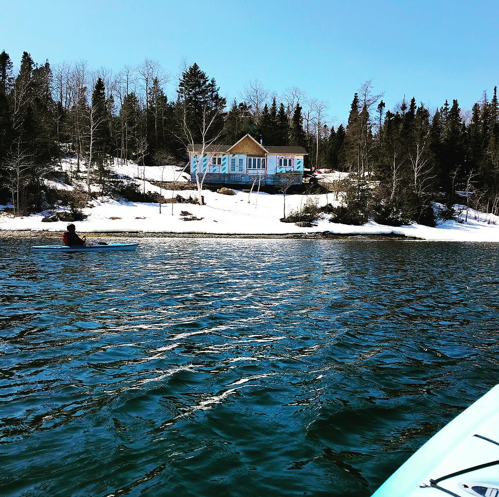 DIY unfinished cabin on the ocean as seen from kayaks on the ocean