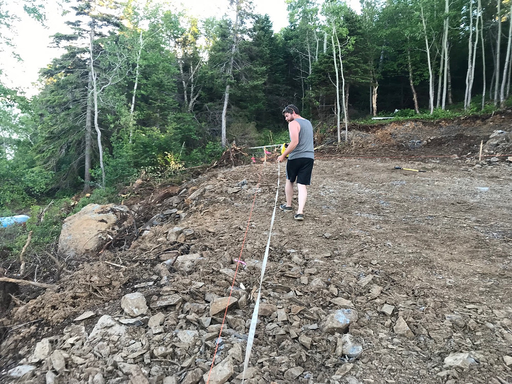 Using a measuring tape to grid out the location of our foundation for our cabin