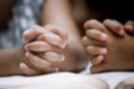 Two Little girl hands folded in prayer on a Holy Bible together  for faith concept in vintage color