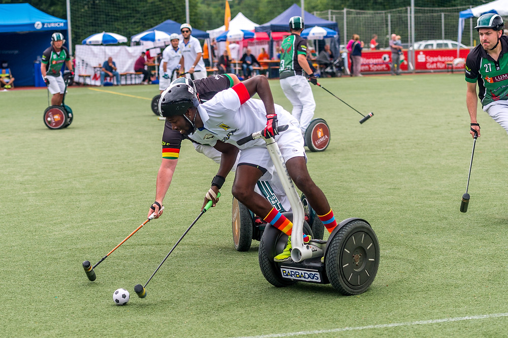 Barbados captain Nevin Roach (centre) in possession of the ball ahead of two players from German team Blade Dragons.