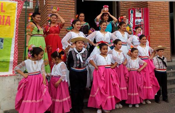 Un grupo de ninos posando vestidos con trajes tipicos de baile en el evento del Dìa del Migrante