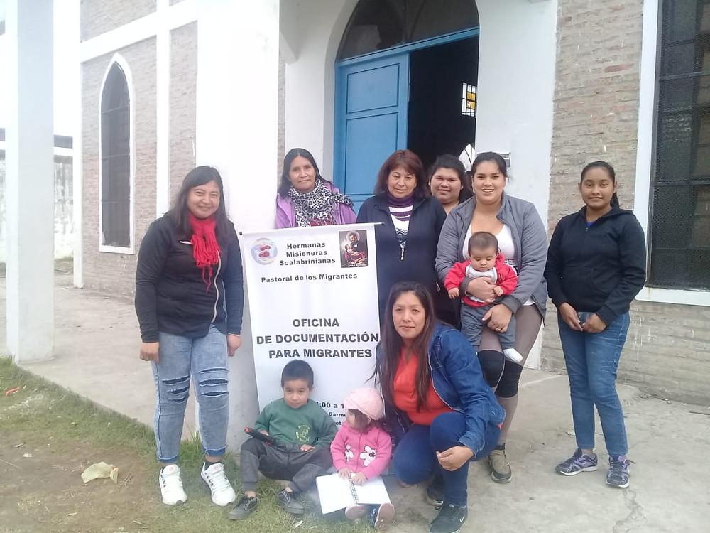 Siete mujeres migrantes sonrientes con tres niños. Juntas en la puerta junto al cartel del Centro Migrante.