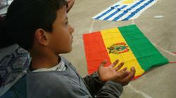 Niño con las manos abiertas frente a diversas banderas.