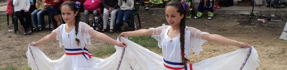 Dos niñas bailando con vestidos amplios.