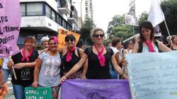 Grupo de mujeres sonrientes sosteniendo carteles.